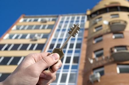 On a background of a modern brick house, hand with keys from an apartment.