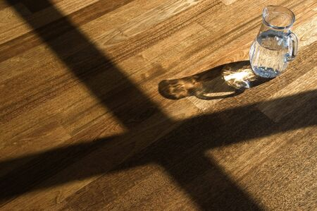 Decanter with water on a wooden floor.
