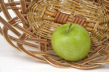 Beautiful green apple on a background of a wum vase.