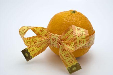 Orange  with measuring tape. White background.