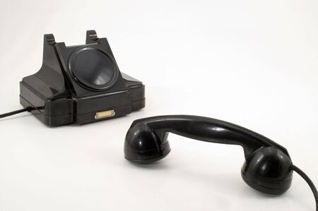 The old telephone of black colour on a white background.