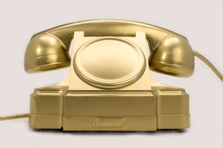The telephone of gold colour on a white background.