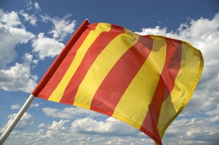The orange striped flag on a background of the dark blue sky with clouds is yellow. Stock Photo