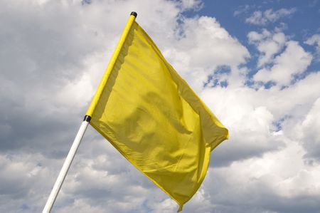 Yellow flag on a background of the dark blue sky with clouds.