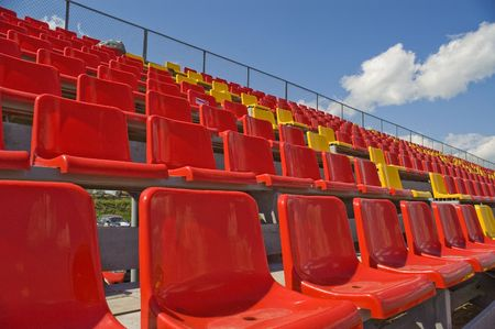 Red and yellow seats on a background of the sky with clouds.