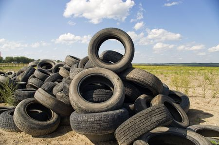 A lot of Wheel Tires dumped in a landfill. Stock Photo