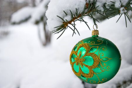 Green  christmas glass ball hanging on the tree in snow.