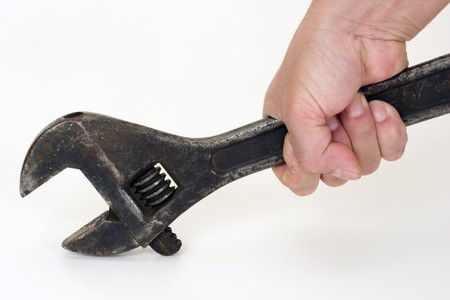 Old spanner in a hand on a light background.