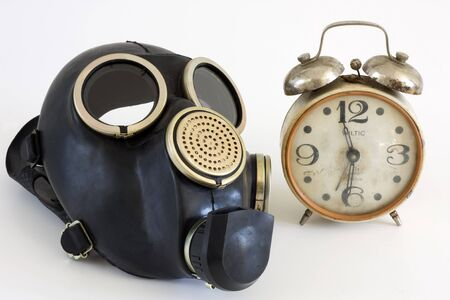 The Gas mask and old watch on white background.