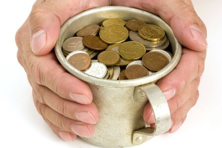 The Male hand keeps get old aluminum mug with money. Stock Photo