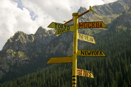 The signpost from meta indicating a managements seven large cities of the world, on a background of mountains.