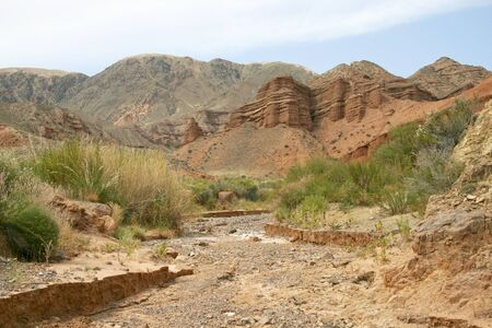 Dry channel of the river on a background of red mountains. Stock Photo - 13681377