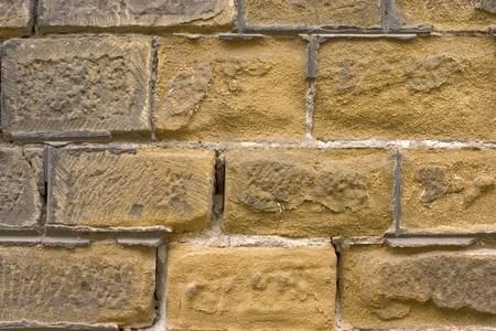 Old wall of a yellow brick. Standard-Bild