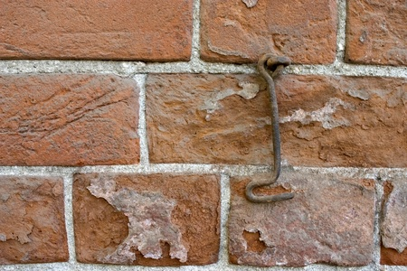 Brick wall and old metal hook. Stock Photo