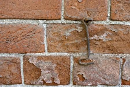 Brick wall and old metal hook. Standard-Bild