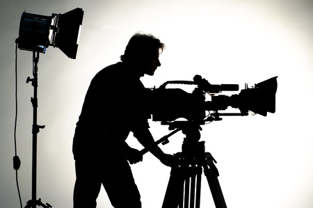 cameraman: Searchlight and silhouette of the camera and cameraman. Stock Photo