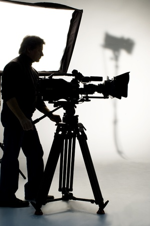 Searchlight and silhouette of the camera and cameraman. Stock Photo