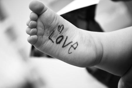 pie bebe: El pie del bebé s con la palabra amor escrito en él Foto de archivo