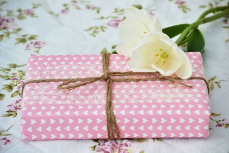 Gift with pink wrapping with two white tulips Stock Photo - 13557241
