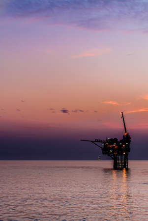Oil platform silhouette when sunset in the sea photo