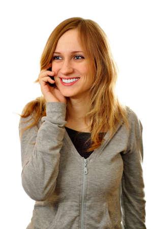 amigas conversando: La mujer sonr�e mientras que teniendo una conversaci�n amistosa en el tel�fono celular