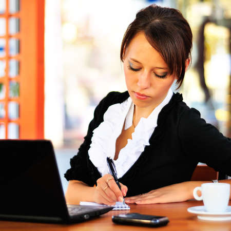 Businesswoman writing something to the notepad photo
