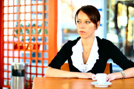 Cute female at the cafe drinking coffee photo