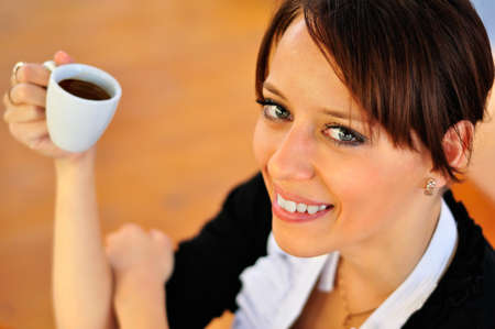 Woman with a coffee at the wooden background  Shot from the top photo