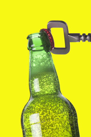 ported: Abrir la botella de cerveza con el abridor de metal en color amarillo Foto de archivo