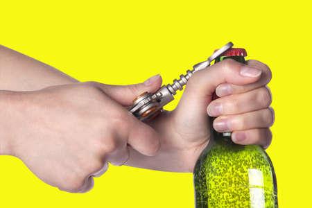 ported: mano que sostiene y la apertura de la botella de cerveza con el abrelatas del metal