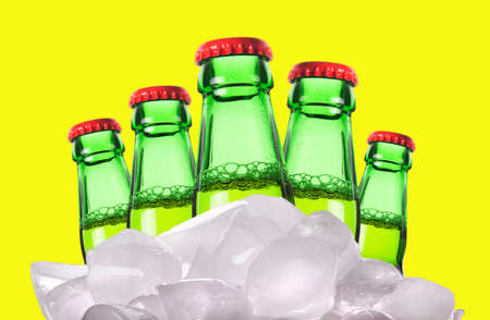 ported: beer bottles with ice isolated on a yellow background