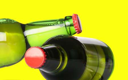 ported: green beer bottles with red caps isolated on a yellow background