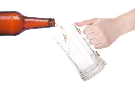 beer pouring from bottle in to the glass with hand isolated on a white background photo