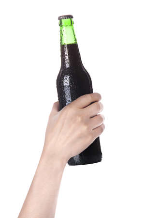 dewed: hand holding Bottle of dark beer with drops isolated on a white background Stock Photo