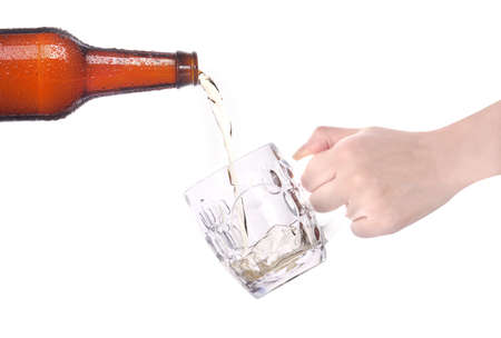 beer pouring from bottle in to the small mug with hand isolated photo