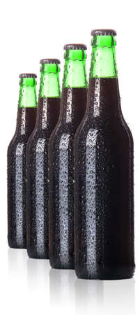 row of dark beer Bottles with drops isolated on white background. photo