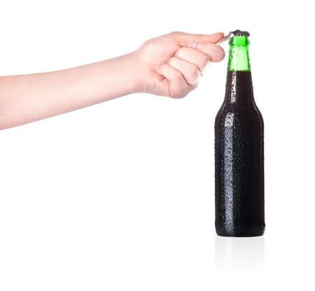 ported: mano que sostiene y la apertura de la botella de cerveza con el abridor de metal