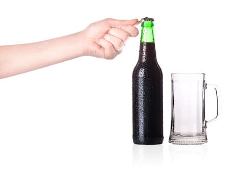 hand holding and opening beer bottle with metal opener photo
