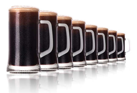 Frosty glass of ldark beer isolated on a white background. photo