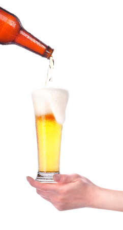 beer pouring from bottle in to the glass with hand isolated photo