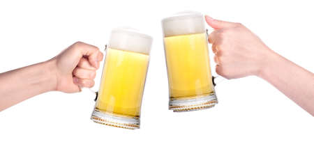 vasos de cerveza: Un par de vasos de cerveza con la mano haciendo un brindis aislado en un fondo blanco Foto de archivo