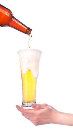 beer pouring from bottle in to the glass with hand isolated Stock Photo - 14556366
