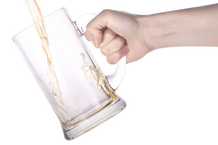 beer pouring in to the big glass with hand isolated on a white photo