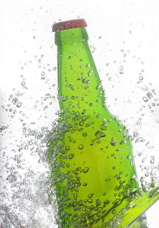 green beer bottle splashing photo