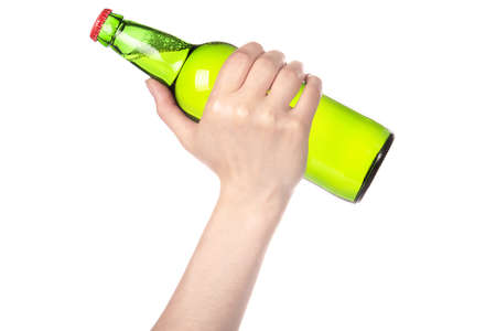 Frosty fresh bottle of beer in a hand isolated  making toast on a white background photo