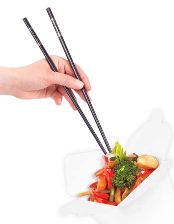 sautee: Sano cibo cinese in un contenitore con le bacchette mano della holding della donna isolato
