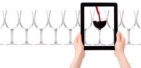 head start: glass of red wine on tablet computer screen isolated on a white background