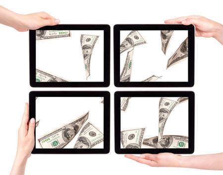 lot of money on a Tablet pc screen with woman hands isolated on a white background photo