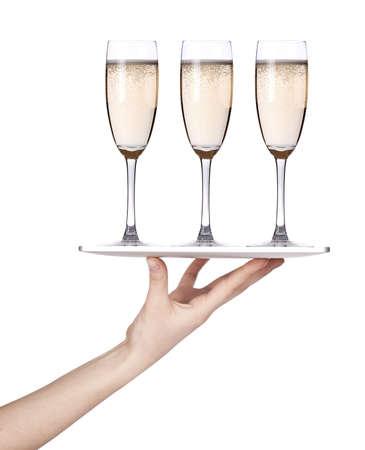 Serveersters hand die een zilveren dienblad met champagne geïsoleerde