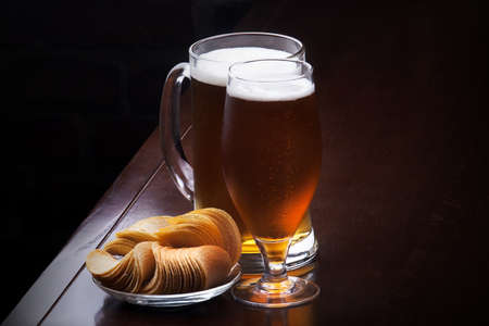 background with glass of Fresh Beer and plate full of chips photo